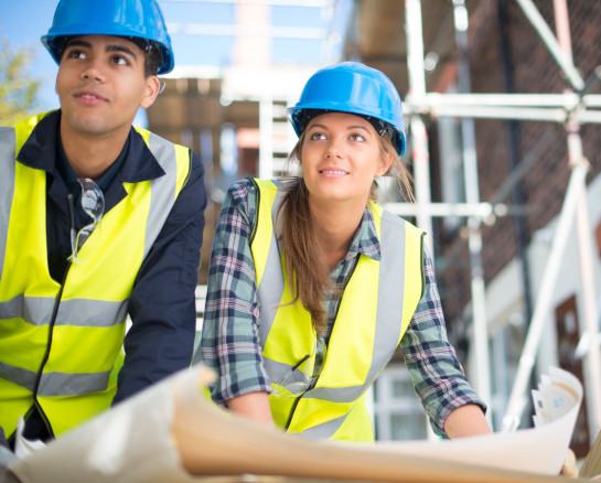 Man and woman in hard hats with hi vis jackets
