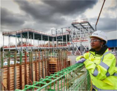 female construction worker wearing hard hat and hi vis jacket