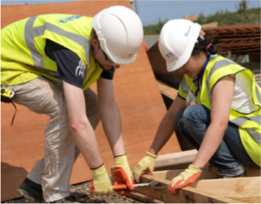 male and female construction workers working on roof wearing hard hats and hi vis jackets