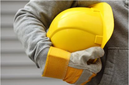 Person wearing gloves carrying a hard hat