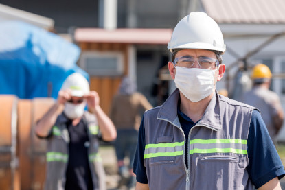 construction workers in hard hats wearing masks
