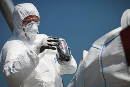 person in white bio hazard suit disposing of asbestos