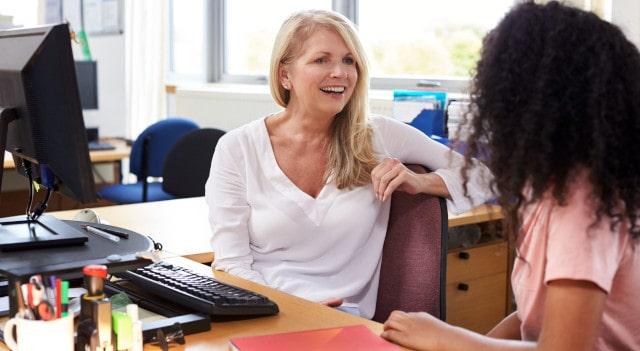 2 women talking at a desk