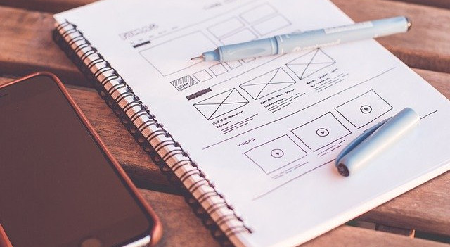 notepad with web design notes and mobile phone
